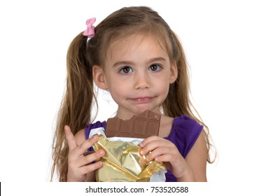A four-year-old girl eats chocolate and makes a gesture. Photographed on a white background