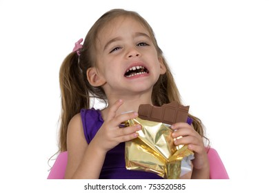 A four-year-old girl suffers from toothache while eating chocolate. Photographed on a white background