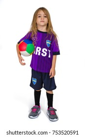 A four-year-old girl Tom Boy is dressed in the style of a footballer and holds a ball in her hand. Photographed on a white background