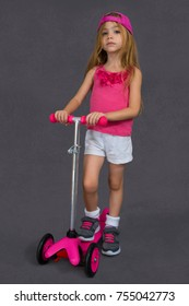 A four-year-old girl wears a sporty style and holds a children's scooter. Photographed on a white background