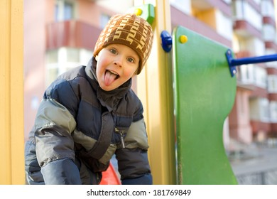 Four-year-old kid plays at a playground in the winter