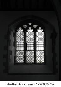 FOWEY, CORNWALL, UK – JULY 18, 2019: Diamond patterned leaded glass window inside the historic St Fimbarrus Church, the Parish Church of Fowey