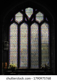 FOWEY, CORNWALL, UK – JULY 18, 2019: Stained glass window with floral patterns inside the historic St Fimbarrus Church, the Parish Church of Fowey