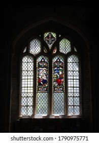FOWEY, CORNWALL, UK – JULY 18, 2019: Diamond patterned leaded glass window depicting biblical narratives inside the historic St Fimbarrus Church, the Parish Church of Fowey