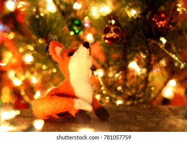 Fox. New years greetings background. Fancy handmade toy from wool on bokeh Christmas background. Place for insert logo or write text. Copyspace for congratulations.