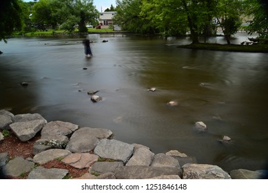 The Fox River lined with trees and rocky shoreline with a fisherman shown in blurred motion created by a time exposure to show movement making a special effect.