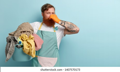 Foxy bearded man covers nose, holds pile of dity laundry in basin, smells unpleasant stinch, has tattoo on arm, has to do washing, isolated over blue background, free space aside for your advert