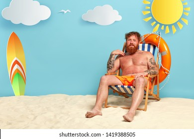 Foxy dissatisfied man gets sunburned at beach, has red skin, sits at sun chair half naked, has tattooed arms, life ring and surfboard, white clouds needs lotion for body. Sun skin care concept