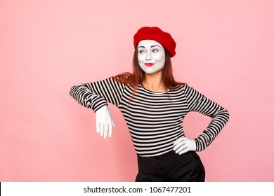 Foxy woman looking away with cunning face. Clown, artist , mime. Studio shot, pink background
