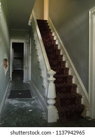 Foyer and staircase inside an abandoned farmhouse. Natural light.