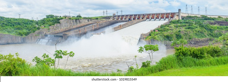 Foz do Iguaçu, Brazil - January 08, 2018: Panoramic view of Itaipu dam concrete structure with the open gates and a enormous stream of water passing through. Clean and renewable energy.