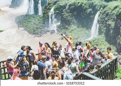Foz do Iguacu, Brazil - January 07, 2018: Tourists on the observing deck of the Cataratas do Iguacu taking selfies and enjoying the view.