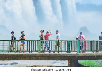 Foz do Iguacu, Brazil - January 07, 2018: Tourists on the footbridge of the Cataratas do Iguacu. The footbridge passes above the Iguacu river waters near to the Cataratas waterfalls.