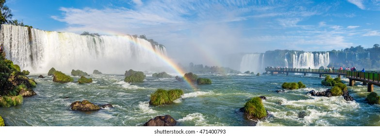 Foz do Iguacu, july 9, 2016: Cataratas waterfalls view from the bottom with some rocks covered by grass in front of the waterfall and bright blue sky as background