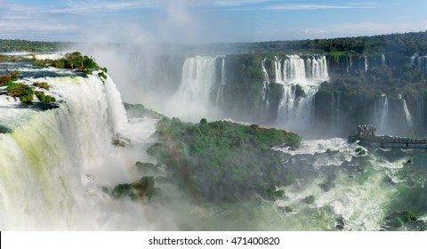 Foz do Iguacu, july 9, 2016: Cataratas waterfalls view from the top with some rocks covered by grass in near the waterfall and bright blue sky as background