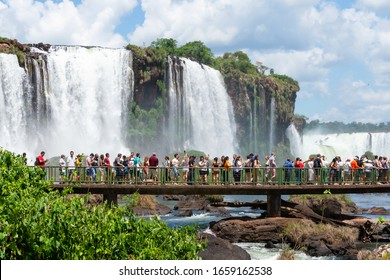 Foz do Iguassu / Brazil - February 23 2020: Crowd of tourists in a walkway visiting Iguazu Waterfalls, also know as Cataratas do Iguaçu. Beautiful natural landscape in South America forest.