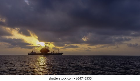 FPSO facility with drilling rig in offshore oil field with beautiful cloudy sunset golden sky background