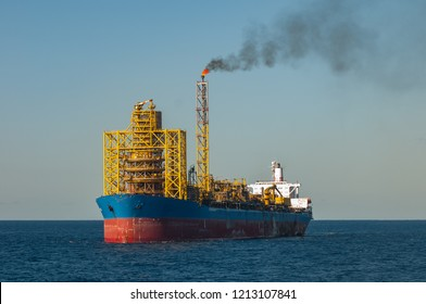 FPSO oil ship platform (floating production storage offloading) with flare burning gas sending smoke to atmosphere, Campos Basin, Rio de Janeiro, Brazil.