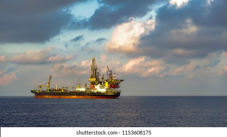 FPSO ship and drilling rig in offshore oil field with beautiful cloud and blue sky background