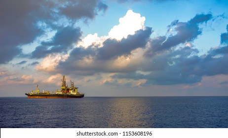 FPSO ship and drilling rig in offshore oil field with beauty cloud and blue sky background