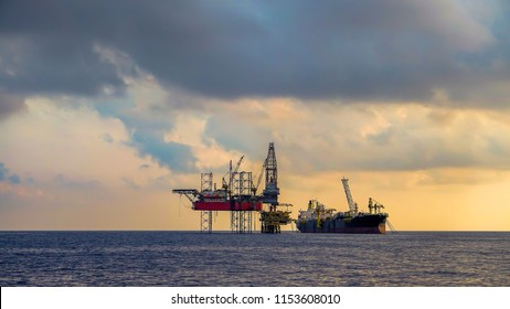 FPSO ship and drilling rig work on oil production platform offshore oil field view with beautiful cloud and blue sky background