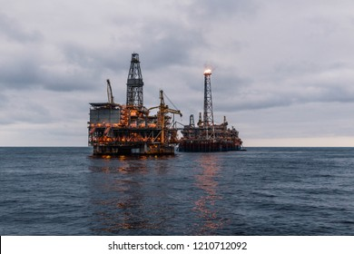 FPSO tanker vessel near Oil Rig platform. Offshore oil and gas industry. Flare is burning with smoke. Environmental pollution