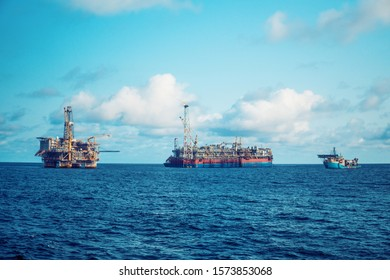 FPSO tanker vessel near Oil Rig platform. Offshore oil and gas industry. Flare is burning with smoke. View from supply vessel