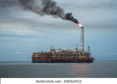 FPSO tanker vessel. Offshore oil and gas industry. Flare is burning with smoke