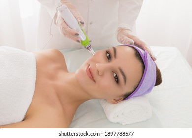 Fractional mesotherapy.A young beautiful woman in the cosmetologist's office receives fractional mesotherapy for her face. Facial skin rejuvenation. Acne treatment. Hardware cosmetology. Beautician.
