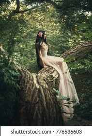 fragile girl, in a transparent dress, sits on a green summer spring tree. Unreal long hair. Artistic Photography. peach nude color long vintage creative clothing silk gown. forest spirit young nymph