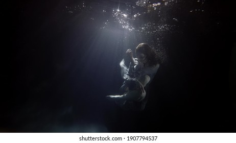 fragile and graceful woman is floating in dark water of swimming pool, mysterious subaquatic shot
