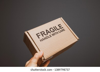 Fragile handle with care warning text on small cardboard with text sign in man's hand against gray background - transportation of delicate objects and good - vintage color cast.