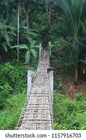 A fragile hanging bridge made up on bamboo in the forest.