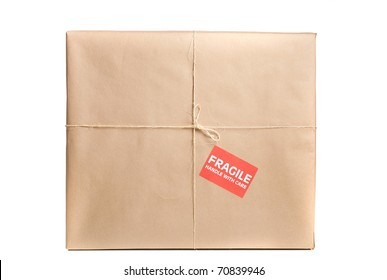 Fragile package wrapped in brown craft paper with label and string on it