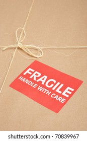 Fragile package wrapped in brown craft paper with label, tag and string on it,