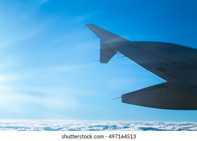 A fragment of an airplane wing with bright blue sky and clouds seen through an airplane window