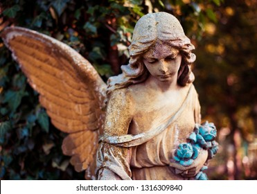 A fragment of ancient sculpture angel in a golden glow in the old cemetery. Symbol of love, invisible forces, purity, enlightenment, ministry. Chariot. Retro vintage style.