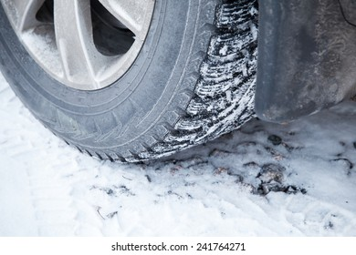 Fragment of automotive wheel with studded tires and winter snowy road