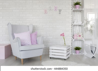 Fragment of a baby room with a white brick wall and DIY furniture made of wooden boxes