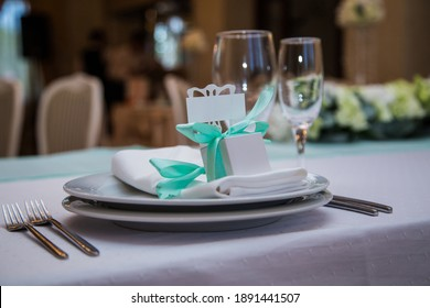 Fragment of a banquet table in mint tones of decor with a seating card with space for text.
