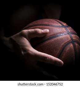 Fragment of a basketball ball in a hand of the basketball player