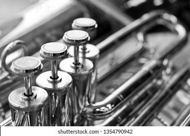 Fragment of a bass tuba valves closeup in black and white