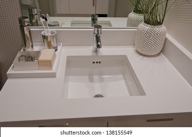 Fragment  of a bathroom, washroom with washbasin (sink) and  some assets such as toothbrush, soap and the decorative vase on the counter. Interior design.