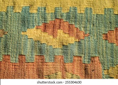 A fragment of a beautiful and coloured traditional handmade turkish carpet with geometrical shapes and green, yellow, red colors
