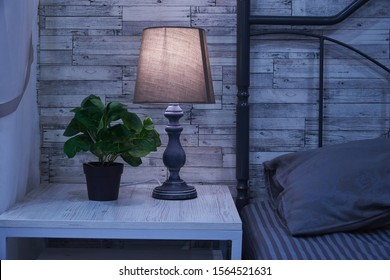 Fragment of a bedroom with a bedside table and a bed. A table lamp and a houseplant are on the nightstand