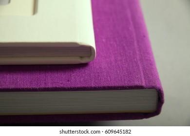 Fragment of binding of photobooks. Purple and white photo book.