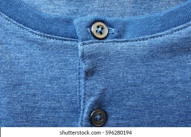 Fragment of blue cotton t-shirt with buttons close up.