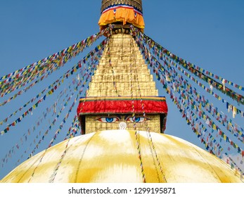 Fragment of Bouddha Stupa with spire and Buddha's eyes on base of spire on a background of prayer flags and clear sky, Kathmandu, Nepal