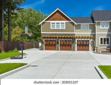 Fragment of brand new farmer's house with three garage doors and concrete driveway in front and blue sky background. Basketball ring in front of huge farmer's house.