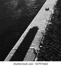 A fragment of a canal embankment with a shadow of a pillar, and a pigeon. Russia, St. Petersburg, August 2015.